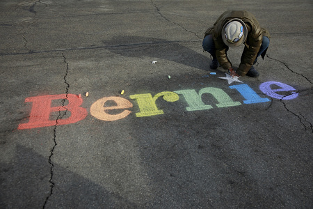 "CEDAR RAPIDS, UNITED STATES - FEBRUARY 3, 2020: A supporter writes, ""Bernie,"" in chalk before Democratic Presidential Candidate Bernie Sanders speaks at the Ceder Rapids field office."