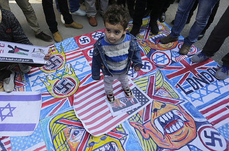 A Palestinian child stands on the illustrations of the British Union flag, the Israeli flag, and an American flag during a protest against the American peace plan in the Middle East, in Gaza City.