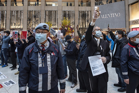 A security guard with a face mask during a protest calling on the government to close the border with China.  Dozens of demonstrators protested at the Landmark shopping mall in Central demanding for the Hong Kong government to close all the borders in Hong Kong connecting with Mainland China in order to control the deadly Corona virus from spreading into Hong Kong.
