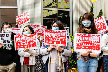 Hospital workers hold placards while wearing surgical masks during the strike in Hong Kong. Hong Kong hospital staff strike to demand closure of China border amid coronavirus fears.