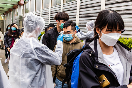 A volunteer measures a passenger's body temperature. In light of a coronavirus outbreak in China, Hong Kong district councillors and residents formed makeshift quarantine stations, screening passengers arriving from China. Citizens measured passenger's temperatures and offered hand sanitizer.