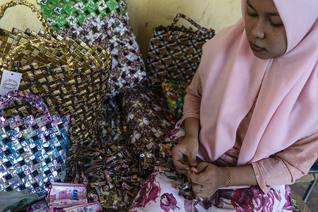 Raihanul Ulfa making the craft bags. Raihanul Ulfa, 24 years old makes craft bags at her home in keude krueng from plastic packaging waste collected from stalls and a number of landfills. The craft bags making was started in the past two years to supplement the economy.