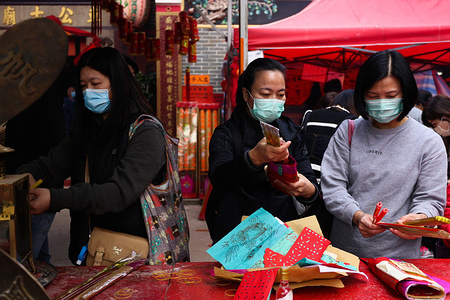 Women prepare to light incense and candles for gods of health as they wear surgical masks following the outbreak of the Wuhan Corona virus. As of early February, one death and 18 cases of 2019-nCoV have been reported in Hong Kong (with the suspicion of local transmission).