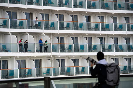 Passengers looks on as a photojournalist reporting on the news related to this cruise ship. Hong Kong authorities are keeping 3,600 passengers and crew members under quarantine on the cruise ship World Dream after three previous travelers were diagnosed with the novel coronavirus.