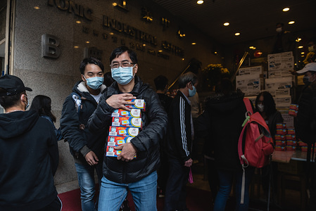 Customers purchase boxes of face masks after the was store opened. Thousands of Hong Kong residents waited overnight for a store selling face masks to open. Customers were only allowed to purchase two packs of masks per person. Some customers ended up waiting for over 20 hours for the store to open.