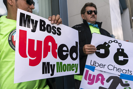 LOS ANGELES, UNITED STATES - FEBRUARY 5, 2020: Uber and Lyft drivers hold placards during a protest against the ridesharing companies' low wages in Los Angeles, California. The drivers called on Uber and Lyft to enforce California Assembly Bill AB5.