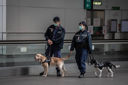 Police agents wear surgical masks at Hong Kong International Airport in Hong Kong. Another day in Hong Kong during the corona virus outbreak. Community outbreak declared in the city: the government said all travellers from the mainland China, including Hong Kong residents would be placed on a mandatory 14-day quarantine as part of its escalated response to the contagion.