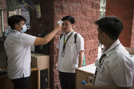 A university student measures the body temperature of a fellow student following the outbreak. Filipinos continue to remain anxious over a new coronavirus known as 2019-nCoV which originated in Wuhan, China in December 2019. The Philippines' Department of Health announced the country's first death due to the virus on 2 February - the first reported death outside of China. The number of 2019-nCoV cases worldwide has already surpassed that of the 2003 Sars epidemic, with the death toll now over 550.