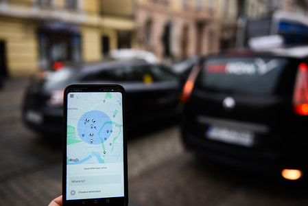 In this photo illustration an Uber app seen displayed on a smartphone with a street in the background.