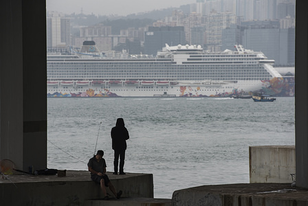 HONG KONG, CHINA, FEBRUARY 8, 2020: Men fish while behind stands at large the Dream World cruiser docking at Kai Tak Cruise Terminal in Kowloon Bay, Hong Kong. Authorities are keeping 3,600 passengers and crew members under quarantine
