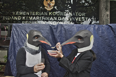 Greenpeace volunteers wearing Penguin masks sit in front of the Coordinating Ministry for Maritime Affairs and Investments building during the campaign. Greenpeace is campaigning for an ambitious global agreement that enables the creation of a network of marine sanctuaries, free from dangerous human activities, which scientists say need to reach 30% of the world's oceans by 2030 to allow the marine wildlife population to recover.