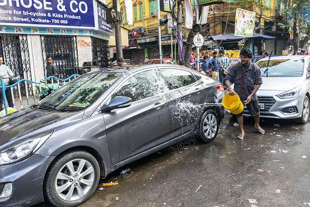 A man washes a car on a roadside in Kolkata.