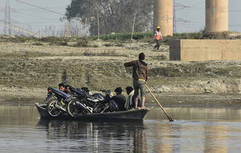 A boat crosses Yamuna Ganga while carrying villagers and bikes.