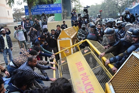 Demonstrators remove a police barricade during a protest against NRC (national register for citizenship) and CAA (citizenship amendment act) which was passed in Indian parliament recently.
