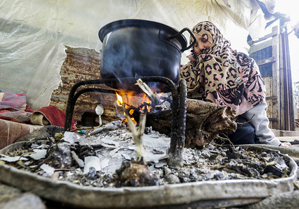 A Palestinian woman cooks food inside a nylon tent on a rainy day at Amal neighbourhood in Beit Lahiya, northern Gaza Strip.