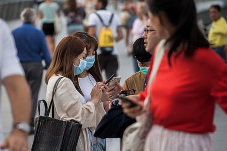 People wearing protective surgical masks visit the Merlion Park, a major tourist attraction in Singapore. Singapore declared the Coronavirus outbreak alert as Code Orange on February 7, 2020.