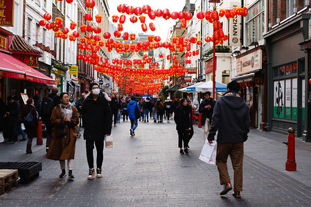 People wear medical face masks on Gerrard Street in Chinatown in London.  Around the world concern continues over the pandemic potential of the Wuhan coronavirus, now officially designated COVID-19, and responsible for more than 1,100 deaths in China so far. To date, however, just 8 cases of the virus have been confirmed in the UK.