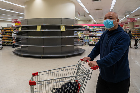 A shopper wearing a protective facemask walks past empty supermarket shelves, usually stocked with toilet paper and kitchen rolls. Panic grows in Hong Kong as the city  has confirmed the 50th case of Novel coronavirus (2019-nCoV). Over 40,000 cases of the virus has confirmed around the world, it has so far claimed over 1000 lives.