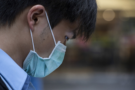 A pedestrian wearing a face mask waits at a traffic light in Central district, Hong Kong. The death toll from the covid-19 coronavirus epidemic passed 1, 100 and infected over 45, 000 people worldwide on February 12.