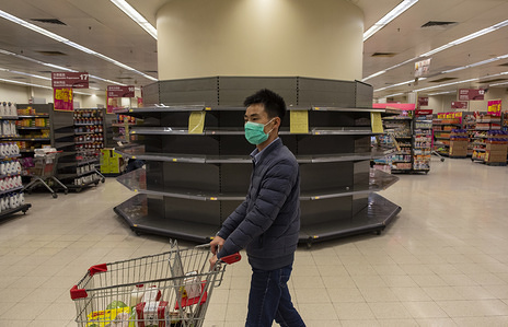 HONG KONG, CHINA, FEBRUARY 12, 2020: A man shopper wearing a face mask walks past empty supermarket shelves, usually stocked with toilet paper and kitchen rolls. The death toll from the covid-19 coronavirus epidemic past 1, 100 and infected over 45, 000 people worldwide on february 12. A shopper wearing a face mask walks past empty supermarket shelves, usually stocked with toilet paper and kitchen rolls. The death toll from the covid-19 coronavirus epidemic past 1, 100 and infected over 45, 000 people worldwide on february 12.