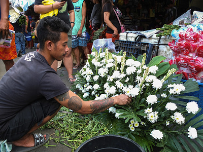 A male flower arranger was busy beating his deadline for flower delivery.