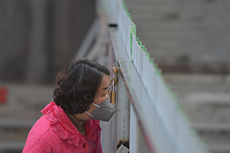 A woman wearing a mask looking out from a gap in an iron fence in a closed community in Fuyang. Local communities has set up closed zones to deny all visitors from visiting in order to minimize the chances of the coronavirus from spreading. On February 13, COVID-19 coronavirus killed more than 1,300 people in China and infected more than 59,000 people.