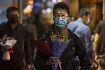 HONG KONG, CHINA - FEBRUARY 14, 2020: Customers carry flowers during Valentine's Day wearing a face mask as a preventative measure against the COVID-19. As of Friday, the death toll from China's coronavirus virus epidemic surpassed 1,400 and 60,000 infected  after new reporting methods were adopted.
