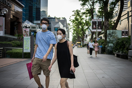 A couple wearing protective face masks walk along Orchard Road, a famous shopping district in Singapore, on Valentine's Day. Singapore declared the COVID-19 outbreak as Code Orange on February 7, 2020.