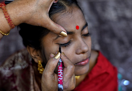 """A bride gets ready for the Marriage Ceremony. An NGO called """"Aloy Phera"""" organised a Mass marriage ceremony of 170 Couples from different religions in kolkata on Valentine's Day to spread the message of love & social harmony. Couples from various backward community who are lacking basic financial support in their family took part in this event."""