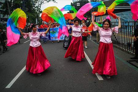 Women dance during the Bandung Rumah Bersama Parade in Asia Afrika Street, Bandung. The parade which was attended by five thousand participants from interfaith and cultural circles was held in order to realize the vision of the City of Bandung.