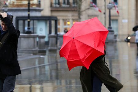 A woman struggles with an umbrella in central London during wet and windy weather. Storm Dennis will bring heavy rain and strong winds across the UK throughout the weekend.