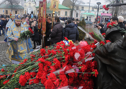 Priest laying flowers during the event. Wreath laying ceremony at the monument to the Afghan soldiers on the Day of honouring combatants in other countries and the anniversary of the withdrawal of troops from Afghanistan, in Kiev.