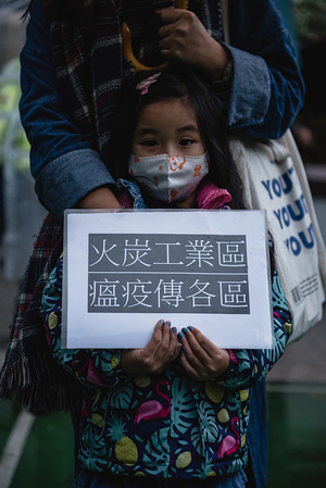 A girl holds a placard during a rally. Residents in Fo Tan gathered to protest the use of a newly finished government housing estate as a quarantine center for Covid19 patients. Many residents had waited months to move in to the public housing estate before the governments' last minute decision to use it as a quarantine center.