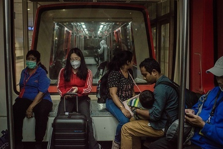 Passengers wear surgical masks inside a train at a departure terminal hall at the Kuala Lampur International Airport. As the number of victims of the new Coronavirus increases, more countries cancel flights within and without the region.