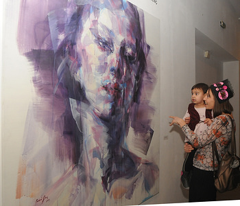 """A visitor examines a painting during the exhibition. Turkish artist, Bedri Baykam presented his curatorial project in a """"Turkish Contemporary Art"""" exhibition in Kiev. The exhibition presents 26 artists of different trends in contemporary Turkish art. The project exposition includes three generations of artists whose work was formed after 1980."""