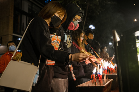 """A couple with protective face masks as a protective measure from the Coronavirus while light up their incenses before entering the Kwun Yum temple during the Kwun Yum Treasury festival. Despite the risk of spreading the Cornavirus, thousands of believers headed to the Kwun Yum temple to pray and ask to """"borrow"""" money from the goddess of mercy Kwun Yum on the night of the Kwun Yam Treasury Festival. In order to control the risk of spreading the Cornavirus the temple authority only allow people wearing face masks to enter the temple."""