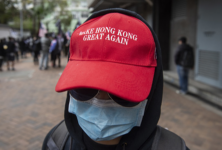 """HONG KONG, CHINA - FEBRUARY 19, 2020: A protester wearing a """"Make Hong Kong Great Again"""" hat takes part in a protest against the use of a quarantine center in Cheung Sha Wan in Hong Kong."""