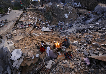 A Palestinian family sit around the fire to warm themselves outside their home that was destroyed by the Israeli army in its latest escalation round in the southern Gaza Strip.