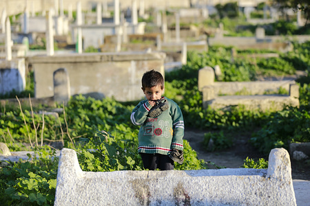 A Palestinian girl stands on a grave at the Sheikh Shaban cemetery where she lives with family, in Gaza City. Dozens of Palestinians live in Sheikh Shaban cemetery due to unemployment and poverty as a result of the Israeli blockade imposed on the Gaza Strip.