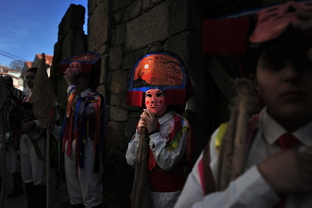 """Chocalerios marching through the streets during the parade. Vilardevos parade is a typical carnival of Galicia, a small town located in the province of Orense, that celebrates carnivals in an ancestral way, chocaleiros (participants) parade through the streets dressed in masks and colourful costumes, sounding their cowbells, called """"chocas"""", touring the town to the sound of music and bands with large drums making all the neighbours rumble."""