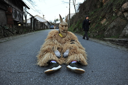 A participant in a costume posing in the street during the parade. Carnival parade of Lazarim a small town of the municipality of Lamego, involves participants with ancestral masks made of acacia wood and costumes of rope wool who wake up to bustle the streets which gives life to rituals that have been repeated since ancient times.