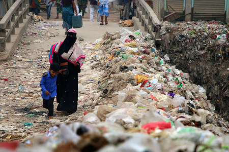 A woman with a kid walk past dumped garbage on the streets of Dhaka. Dhaka City is one of the most polluted cities in the world. ... Industries cause air and water pollution through smoke emission, inadequate solid waste management and dumping of untreated effluent to lakes, rivers and ground water. The arsenic pollution of groundwater has become a major disaster for Bangladesh.