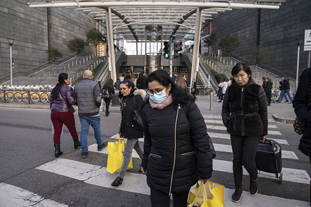 A woman wearing a face mask crossest the street at Porta Garibaldi Station. Precautionary measures, such as wearing face masks have been taken by citizens and tourists in Milan, for dealing with the fear of being infected by Coronavirus (COVID -19), as more than one hundred confirmed cases have been discovered in north Italy and three old people died. According to a regional decree, many activities (educational, cultural, museum tours etc) will be suspended until 1st or 2nd March; thus, people reacted with a massive rush to buy water, food supply and soaps.