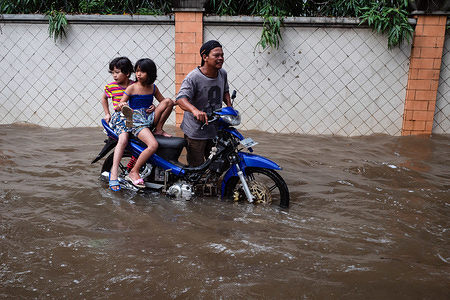 Motorcyclists wade through a flooded road.Heavy rains triggered widespread flood in Jakarta inundating thousand homes.