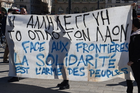 Protesters hold a banner during the demonstration.  Hundred people gather in Marseille to support the migrants and also to protest against the war and conflicts between Greece and Turkey.