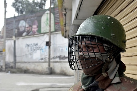 """An Indian paramilitary trooper stands alert during restrictions in Srinagar, Indian administered Kashmir. Authorities imposed restrictions in parts of Srinagar as separatists called for a shutdown against """"brutal killing"""" of Hurriyat leader Muhammad Yousuf Nadeem, shifting political inmates and lifers from Srinagar central jail and staying of FIR against Army Major in Shopian killings by Supreme Court."""