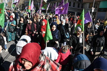 Women march while holding flags during the protest. Kurdish women from Marseille marched through the streets in solidarity with the women of Kurdistan.