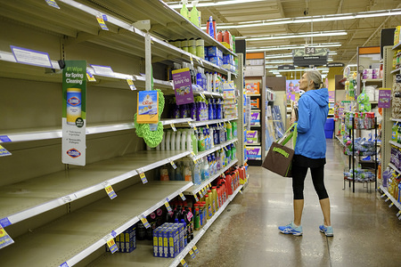 BLOOMINGTON, UNITED STATES - MARCH 11, 2020: A woman shops for cleaning supplies at a Kroger in Bloomington, where shoppers were stocking up on toilet paper, and other items on the day World Health Organization declared Coronavirus to be a pandemic. Toilet paper, wipes, protective breathing masks, and other items are either sold out at local stores, or are in short supply.