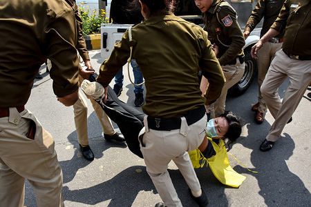 Policemen arrest a Youth Activist during the protest marking the 61st anniversary of the Tibetan Uprising Day near the Chinese embassy in Delhi.