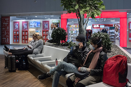Travelers wear face masks as a precaution against the spread of Coronavirus at the Frankfurt Airport. United States president Donald Trump imposed restrictions on arrivals from the European Schengen Area, in efforts to curb coronavirus spread in the US.